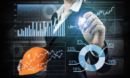 Foto de Businesswoman pointing on 3d financial chart. Woman in business suit standing with safety helmet. Digital technology and innovation in construction industry. Economy and investment data visualization. - Imagen libre de derechos