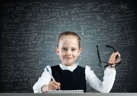 Photo pour Smiling little girl in schoolwear doing her homework. Time to study concept. Happy schoolgirl with glasses sitting at desk and writing in notebook. Research and education in elementary school. - image libre de droit