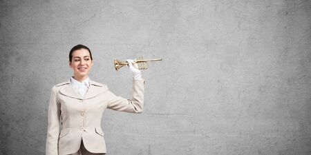 Beautiful woman holding trumpet brass near ear and listening. Young businesslady in white business suit and gloves posing with music instrument on grey wall background. Business concept with musician