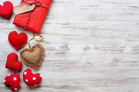 Flat lay cute composition with handmade fabric red hearts. Red gift box on wooden table. Happy birthday or anniversary congratulation. Romantic love story template with copy space.