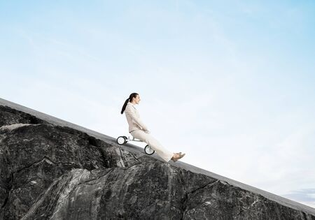 Photo pour Beautiful happy woman riding downhill on mountain road. Young employee in white business suit going down on small bike outdoor. Professional career start. Beginner level business concept. - image libre de droit
