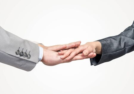 Photo pour Close up of businesspeople putting their hands together against white background - image libre de droit