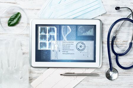 Human genetic research in modern medical laboratory. Tablet computer with DNA helix structure on screen. Stethoscope and cardiogram on wooden desk. Medical diagnostics and patient genome testing.