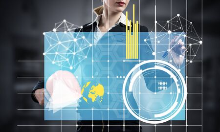 Foto de Businesswoman pointing on 3d financial graph. Woman in business suit standing with safety helmet. Digital technology and innovation in construction industry. Business analytics and data statistics. - Imagen libre de derechos