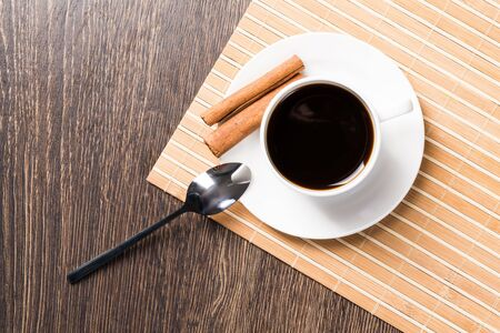 Photo pour Cup of espresso coffee on wooden table. Top view white porcelain cup and cinnamon sticks on saucer. Close up fresh and aromatic hot drink in cafe. Morning coffee and break time concept. - image libre de droit