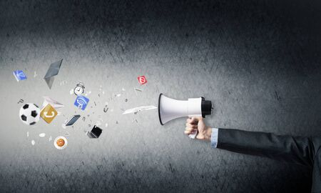 Foto de Businessman hand holding megaphone on wall background. Various things flying out from loudspeaker. Sport competitions announcement and advertisement. Business news broadcasting and online streaming - Imagen libre de derechos