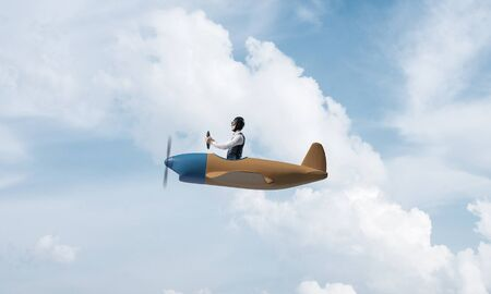 Photo pour Young man in aviator hat with goggles driving propeller plane. Traveling around the world by airplane concept. Funny man flying in small airplane in sky with clouds. Extreme aviation hobby. - image libre de droit