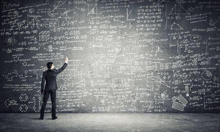 Foto de Businessman or teacher drawing science sketches at blackboard - Imagen libre de derechos
