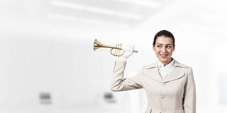 Beautiful woman holding trumpet brass near ear and listening. Young businesslady in white business suit and gloves posing with music instrumentin light office interior. Business concept with musician