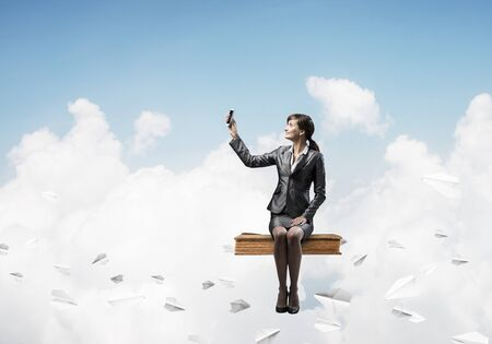 Photo pour Attractive girl sitting on big book and flying in blue sky. Young woman in business suit using smartphone. Pretty businesswoman on background cloudscape panorama with paper planes. - image libre de droit