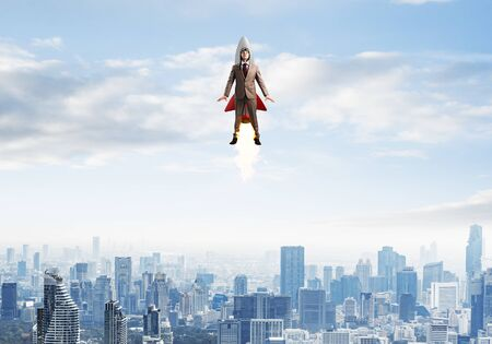 Photo for Businessman in suit and aviator hat flying on rocket. Superhero businessman flying with jetpack rocket in blue sky above modern downtown. Successful business startup. Career growth concept. - Royalty Free Image