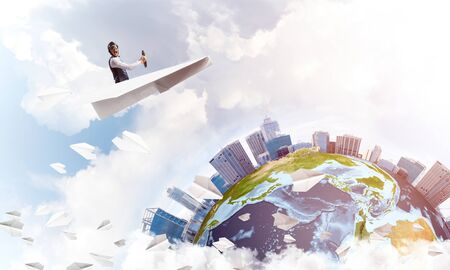 Photo for Pilot in leather helmet and goggles driving paper plane in cloudy blue sky. Funny man flying in small paper airplane over earth globe. Spherical view of modern city with high skyscrapers. - Royalty Free Image
