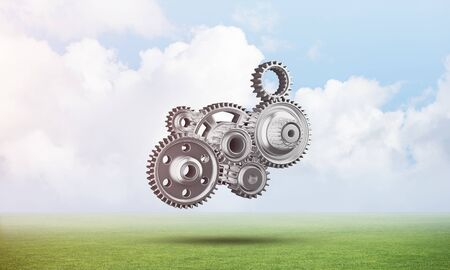 Photo pour Abstract mechanism with cogwheels on green meadow. Construction and manufacturing. Mechanical technology machine engineering. Nature landscape with green grass and blue sky. Mixed media with 3D object - image libre de droit