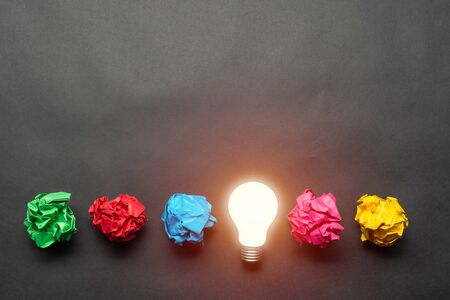 Photo for Lightbulb and crumpled colorful paper balls on black background. Successful solution of problem. Idea generation and brainstorming. Genius idea among failing ideas metaphor. Business motivation - Royalty Free Image