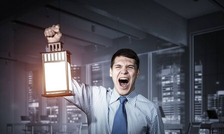 Photo for Screaming businessman holding glowing lantern on background office interior. Front view of emotional man in shirt and tie looking for something in dark. Scared business person walking with lantern - Royalty Free Image