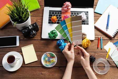 Photo pour Interior designer choosing colors from swatches at wooden desk. Office workplace with laptop and stationery. Selection of color palette for design. Professional house renovation and interior redesign. - image libre de droit