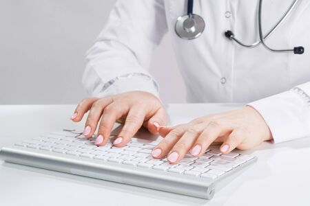 Photo pour Close up doctor typing on computer keyboard. Female physician in white coat with stethoscope sitting at desk. Professional medical diagnosis and treatment in clinic. Healthcare and medicine. - image libre de droit