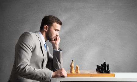 Foto de Businessman moving chess figure in chessboard. Successful management and leadership. Handsome man in business suit at desk with chess on grey wall background. Operative tactics and strategy planning. - Imagen libre de derechos