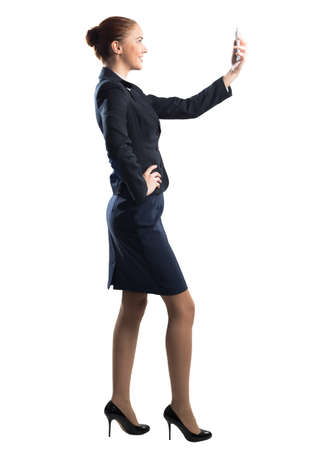 Photo pour Young beautiful woman taking selfie photo with smartphone. Confident and stylish businesswoman in dark blue suit. Corporate businessperson isolated on white background. Mobile communication layout. - image libre de droit