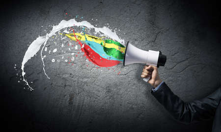 Foto de Businessman hand holding megaphone on wall background. Colorful paint splash flying out from loudspeaker. Event announcement and business advertisement. Social media broadcasting and online streaming - Imagen libre de derechos