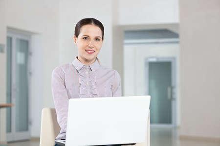 Photo pour Attractive young woman works with a laptop - image libre de droit