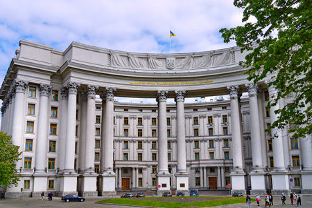 Facade of the Ministry of Foreign Affairs of Ukraine against the blue sky. Patriotically, the flag flies from the wind on the roof