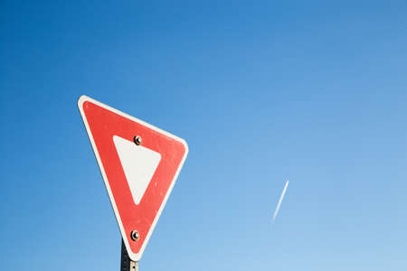 Foto de Yield sign against a blue sky with a contrail. - Imagen libre de derechos