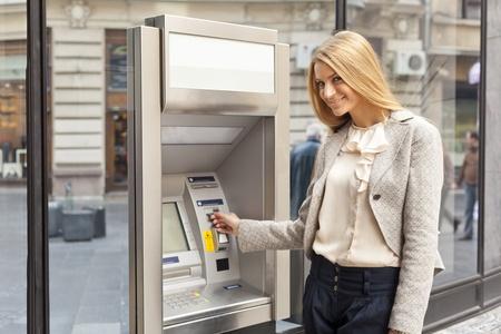 Photo pour Young Woman using Bank ATM cashe machine on the street - image libre de droit