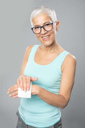 Photo pour Senior woman cleaning hands with wet wipes - care for health and prevention of infectious diseases stock photo - image libre de droit