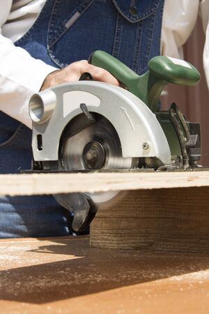 Photo for Construction worker crosses a board with a circular saw. - Royalty Free Image