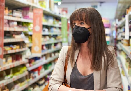 Photo pour Woman buying groceries in supermarket, wearing black medical face mask while shopping in grocery store. Covid-19 virus prevention. - image libre de droit