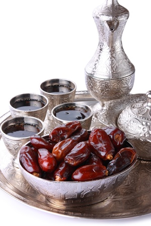 Antique silver pitcher and coffee cup set with dates in a tray isolated on a white background - vertical  Including clipping path