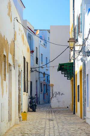 Desert Street in North Africa, Mahdia, Tunisia On the right is a lantern, yellow doors, on the left is peeling paint on the walls