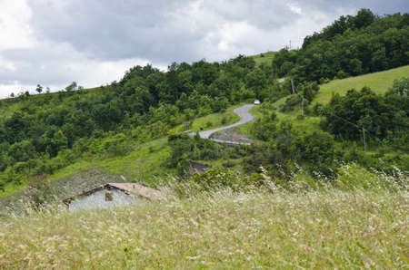 Landscape areas, roof house and winding road into the hills - Cloudy day in summer season - Appennini Modenesi - Region of Emilia-Romagna - Northern Italy - Europe - Travel - Eco Tourism