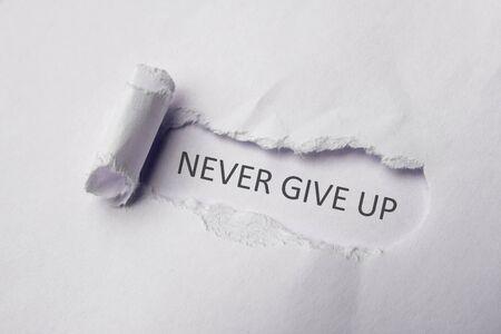 Foto de Never give up on white Torn Paper. Copy space. - Imagen libre de derechos