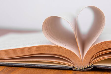 Photo pour Old book and heart-shaped pages. White background - image libre de droit
