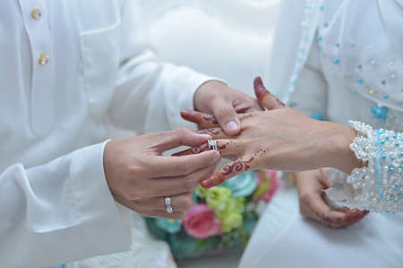 Photo pour malay wedding groom bolstering gold ring on bride's finger - image libre de droit