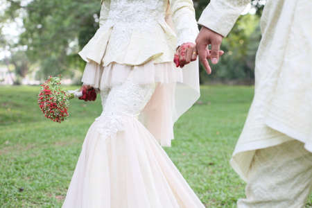 Photo pour Beautiful malay wedding couple wearing traditional clothing on nature green park background. - image libre de droit
