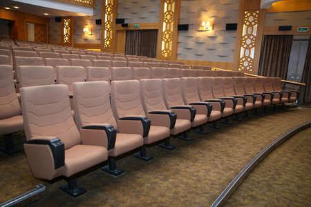 Traditional classically regal ornate rounded wood armed formal plush deep red velvet opera movie theater chairs in curved row with decorative gold molding in fancy carpeted venue.