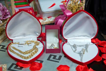Photo pour Gold necklace and ear rings and silver jewelry with pearls being placed and displayed in box with red velvet to be given as a gift to the bride .Gold necklace in a red box in the shape of a heaart - image libre de droit