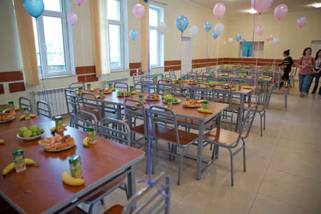 Food aid for orphans . kids eating lunch in a social school orphanage,population are orphans,due . Blue and pink balls on the tables. Bananas, apples, cake .