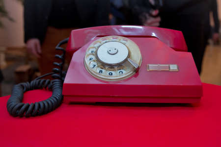 Photo pour Red antique vintage analog telephone dialing or scrolling phone on red table. Contact us concept .Still life with retro red phone on wooden red table over grunge background - image libre de droit