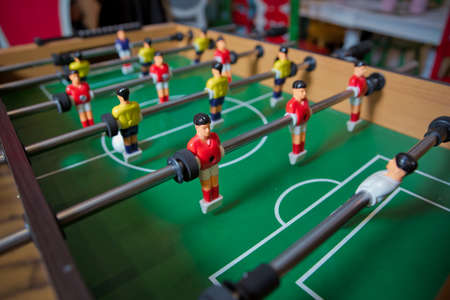 Foto de Soccer table kid's home toys, football family game table toys children's board . Table soccer. Foosball in a children's playroom. Close-up during the game. - Imagen libre de derechos