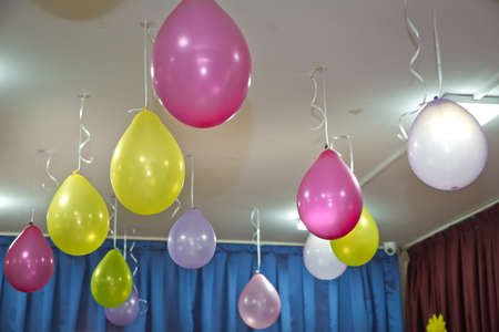 Photo for Helium balloons. Pink and yellow balloons float on the white ceiling in the room for the party. Wedding or children birthday party decoration interior. - Royalty Free Image