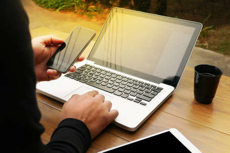 Photo pour Cropped shot Silhouette of a man's hands using a laptop at home, rear view of business man hands busy using laptop at office desk, young male student typing on computer sitting at wooden table, phone on table, coffee, filter sun - image libre de droit