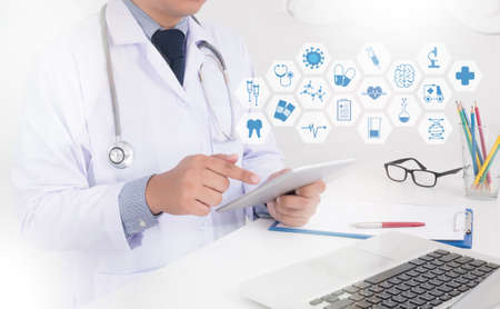 Photo pour Close up of a male doctor in scrubs using digital tablet. Medicine doctor hand working with modern computer interface as medical concept - image libre de droit