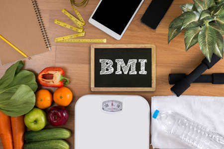 Foto de top view, fitness and weight loss concept, dumbbells, white scale, towels, fruit, BMI body mass index formula rate formula in a board - Imagen libre de derechos