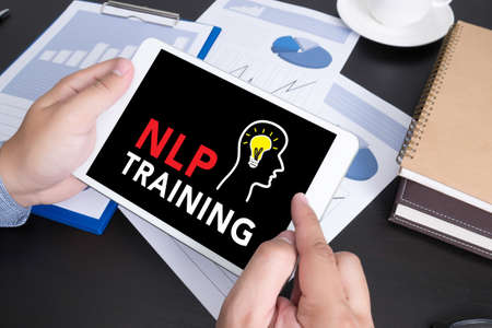 NLP TRAINING CONCEPT Modern people doing business, graphs and charts and touch-pad