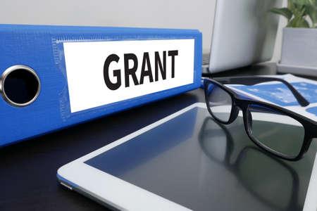 Photo pour GRANT Office folder on Desktop on table with Office Supplies. - image libre de droit