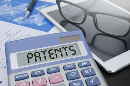 PATENTS Calculator  on table with Office Supplies. ipad